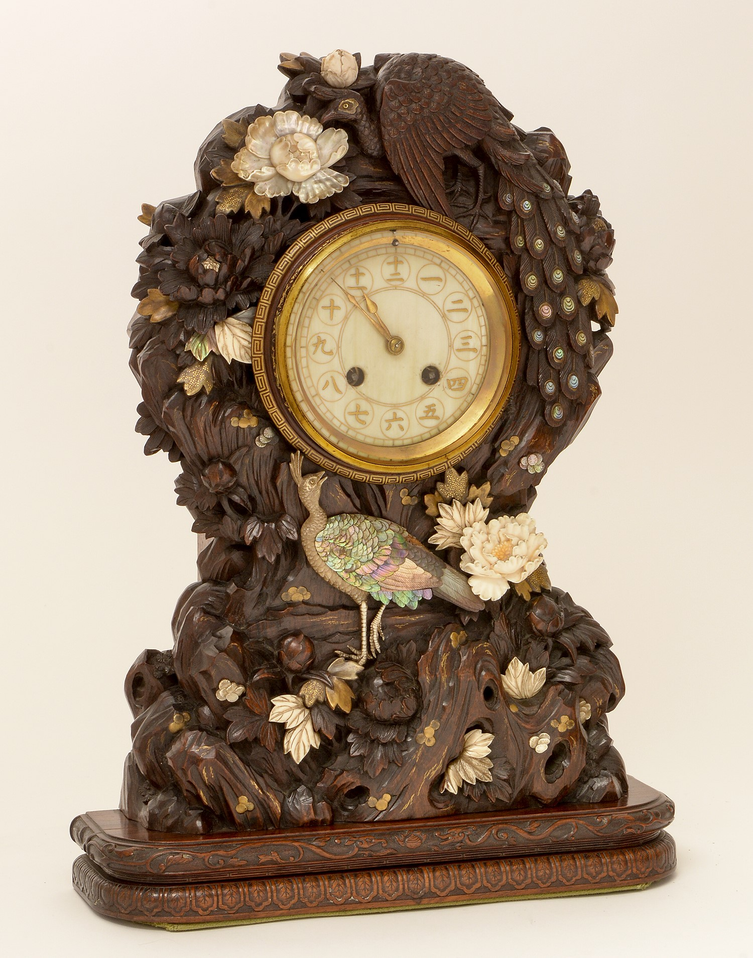 A rare and unusual Japanese carved hardwood and shibayama mantel clock, Meiji period, the circular ivory dial with Kanji numerals, Japy Freres