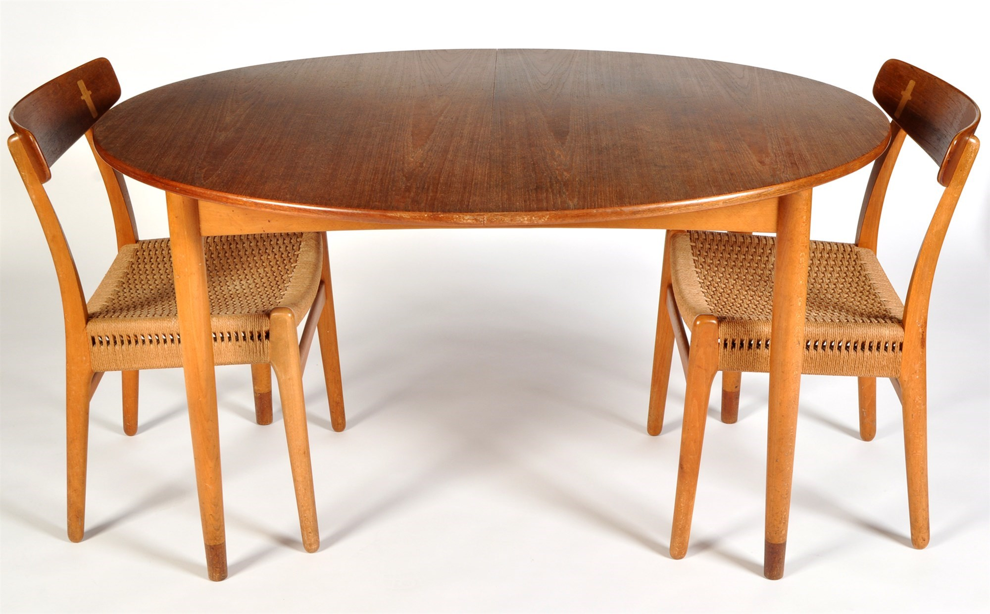 Six Danish teak and beech wood dining chairs, with rush seats, after a design by Hans Wegner, probably Model CH23;