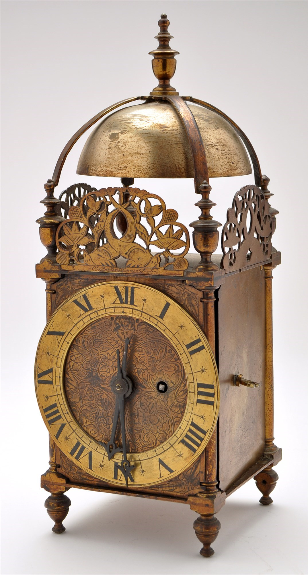 A brass lantern style clock, with engraved dial within roman chapter ring,