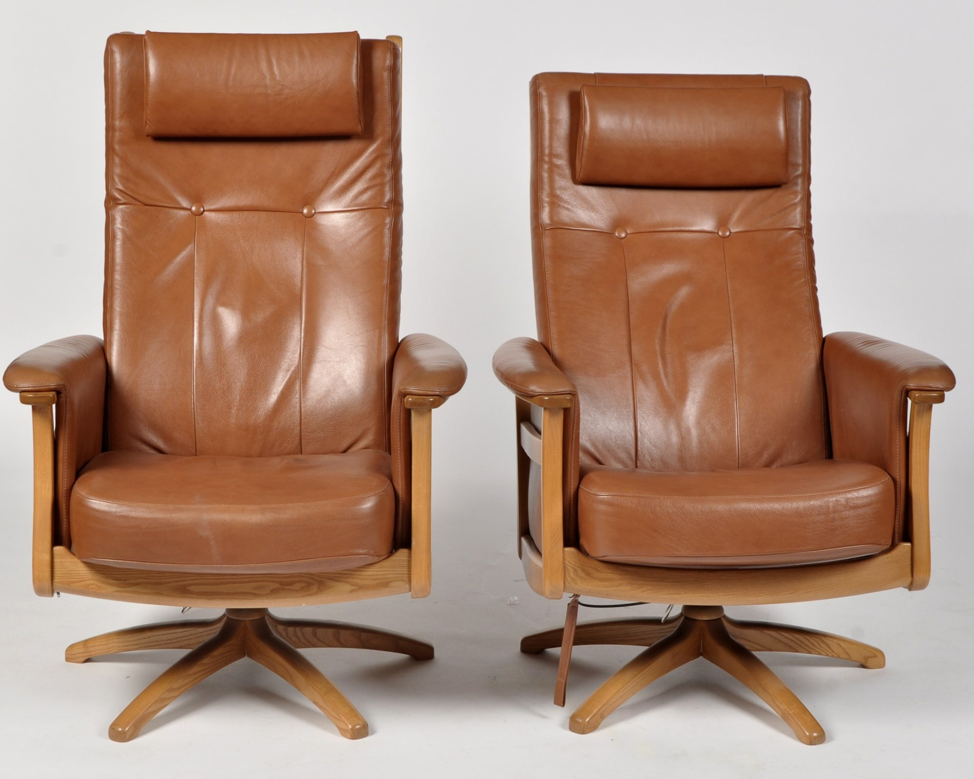 Ercol: two Gina swivel armchairs upholstered in brown leather.