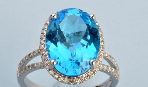 Lot 691-A topaz and diamond cluster ring, the oval...