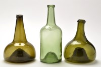 Lot 1029 - Two green glass onion shaped bottles, the...