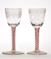 Lot 1036 - Two engraved opaque and red enamel twist wine...