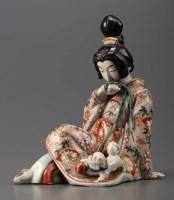 Lot 72 - A Satsuma figure of a seated Geisha holding...