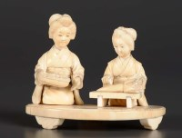 Lot 77 - A carved ivory group of two women kneeling...