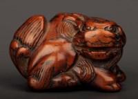 Lot 84 - A carved boxwood netsuke of a shishi lion,...
