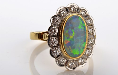 Lot 1096-An opal and diamond cluster ring, the oval...