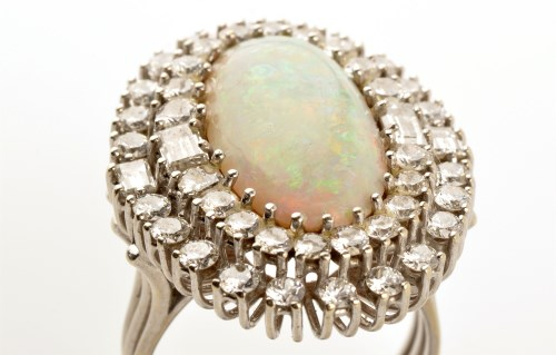 Lot 865-An opal and diamond cluster ring, the central...