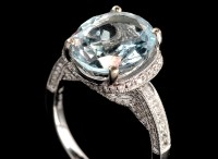 Lot 1003 - An aquamarine and diamond dress ring, the oval...