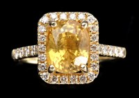 Lot 1006 - A yellow sapphire and diamond cluster ring,...