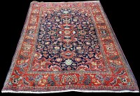 Lot 1063 - A Kashan rug, with bold floral scrolls around...