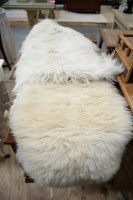 Lot 12 - Two double sheepskin rugs; and another rug,...