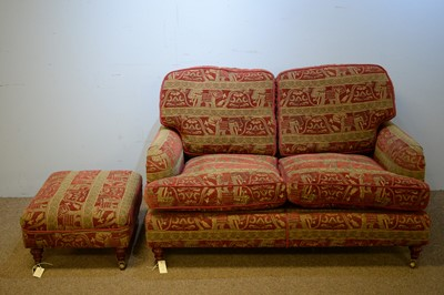 Lot 6 - Two-seater sofa and matching footstool.