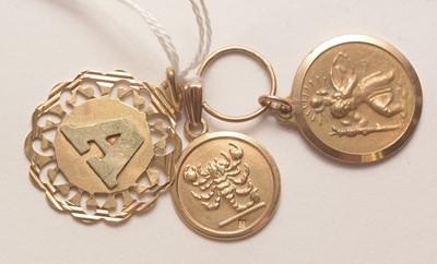 Lot 204 - Three yellow metal pendants.