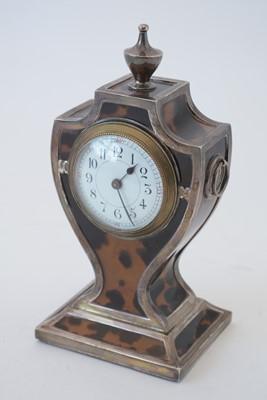 Lot 764 - An Edwardian silver and tortoiseshell mantel timepiece.