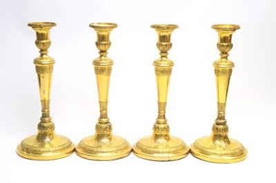 Lot 133 - A set of four Victorian gilt metal candlesticks.