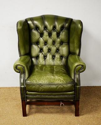 Lot 75 - A 20th Century wingback armchair