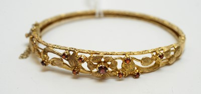 Lot 175 - Garnet set 9ct yellow gold bangle