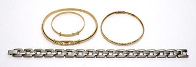 Lot 205 - Three yellow metal bracelets and a titanium bracelet