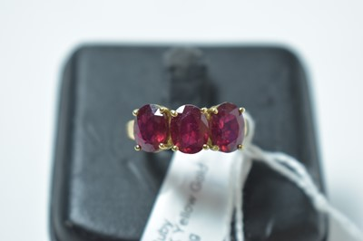 Lot 229 - A contemporary 9ct gold and ruby three stone ring
