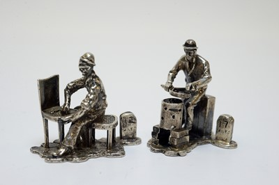 """Lot 90 - A set of seven Elizabeth II silver """"Cries of London"""" figural place card holders."""