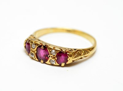 Lot 20 - A three-stone ruby and diamond dress ring.