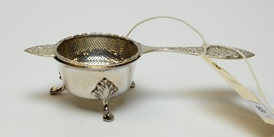 Lot 83 - A George V silver tea strainer and stand.