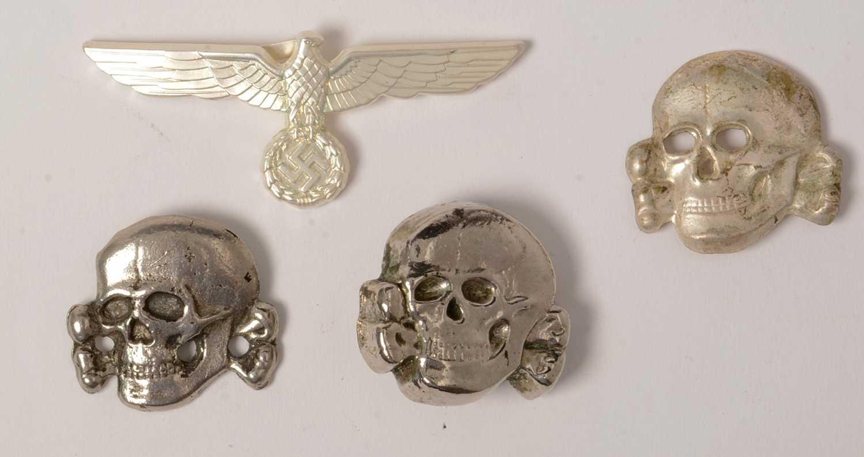 Lot 1049 - Three reproduction WWII SS Toten Kopf badges and a cap badge