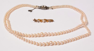 Lot 223 - An early 20th Century diamond, pearl, and yellow-metal bar brooch.