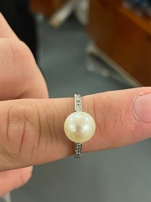 Lot 23 - A high-carat white metal, diamond, and pearl solitaire cocktail ring.