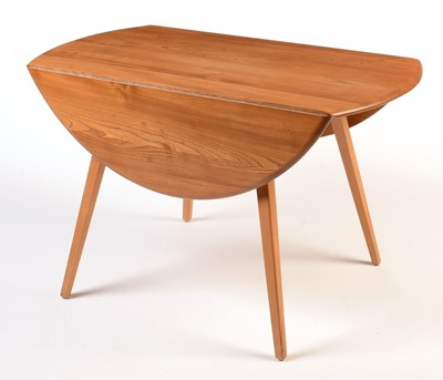 Lot 56 - Ercol: a light beech and elm round-shaped drop-leaf dining table.