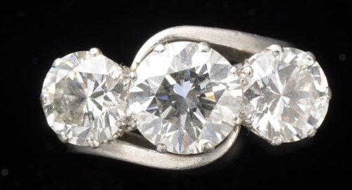 Lot 957-A three stone diamond ring, the central old...
